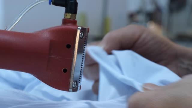vidéos et rushes de ouvrier utilisant une machine en usine - t shirt