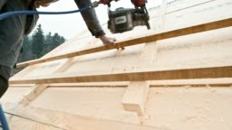 Worker using a pneumatic nail gun to drive nails through batten on the roof