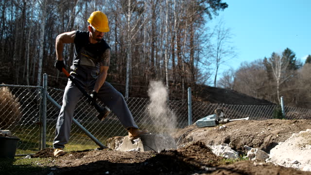 time warp worker using a sledgehammer to strike a concrete block - rubble stock videos & royalty-free footage