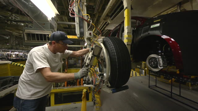 vídeos de stock e filmes b-roll de ms pan worker using an mechanical assist to installing wheel and tire on minivan in an auto assembly plant / princeton, indiana, united states - chassi