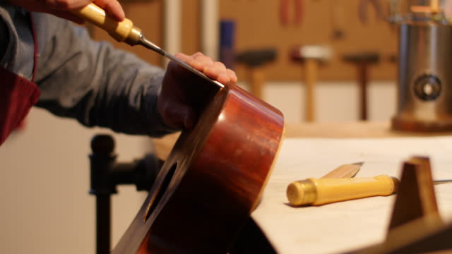 worker using chisel on wood in guitar workshop - ギター点の映像素材/bロール