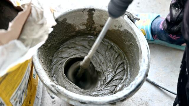 バケット内のモルタル液体を混合する電気セメントスターラーを使用した作業員 - 作業道具点の映像素材/bロール