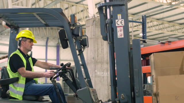 worker using forklift to lift cardboard boxes - forklift truck stock videos and b-roll footage