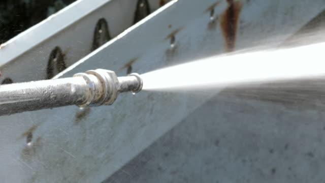 vidéos et rushes de travailleur utilisant une buse d'eau à haute pression dans une usine de traitement de l'eau pour nettoyer le sol. - pression physique