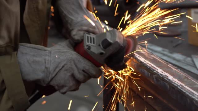 Worker using industrial grinder on metal parts in industrial plant, factory