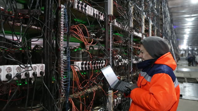 stockvideo's en b-roll-footage met worker using laptop in front of mining rigs operating inside racks at the cryptouniverse cryptocurrency mining farm in nadvoitsy, republic of... - mining