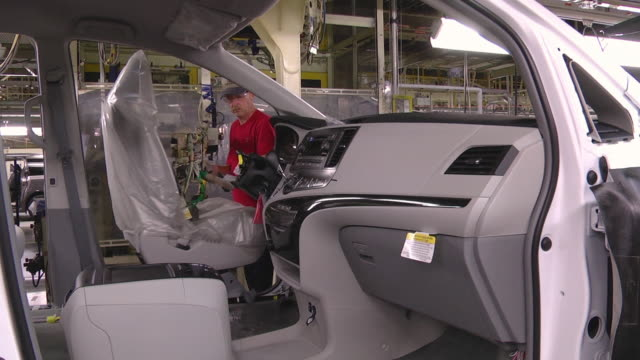 ms worker using lift arm to install driver seat in minivan at an auto assembly plant / princeton, indiana, united states - model kit stock videos and b-roll footage