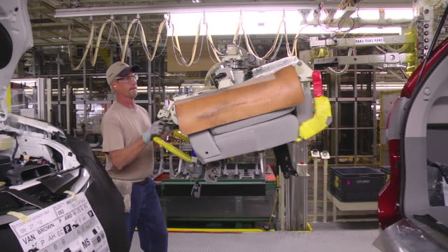 ms pan worker using lift arm to installing rear seat in minivan / princeton, indiana, united states - catena di montaggio video stock e b–roll
