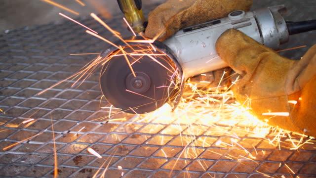 vídeos de stock, filmes e b-roll de trabalhador usando máquina cortando metal líquido com faísca - serra circular