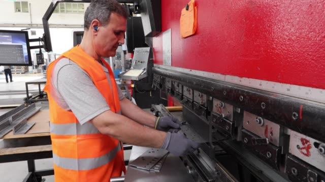 vidéos et rushes de ouvrier utilisant le pliage en métal, pliage et machine de moulage dans une usine - tôle