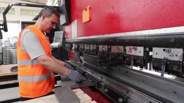 arbeitnehmer, die verwendung von metall, falten, biegen und formteil-maschine in einer fabrik - arbeitsintensive produktion stock-videos und b-roll-filmmaterial