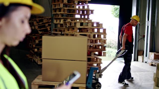 arbetaren använda lastpall jack. kvinna som övervakar arbetet - dra bildbanksvideor och videomaterial från bakom kulisserna