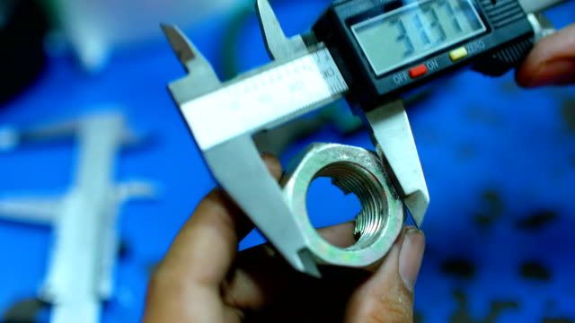 Worker Using Vernier Calliper for Measuring Scale of Nut