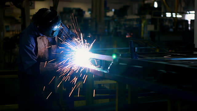 Worker using welding machine on his work.In the automotive parts industry.