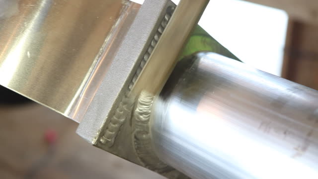 Worker Using Wire Brush to Clean Aluminum TIG Weld