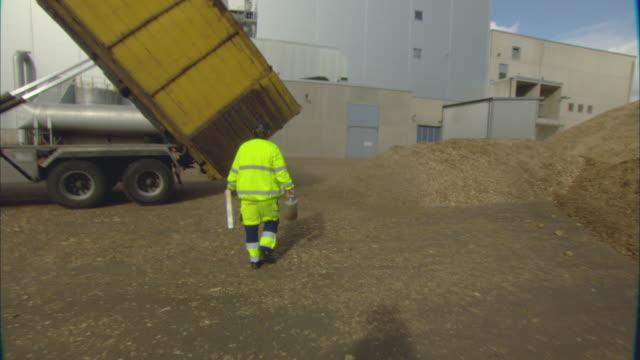 ws pov worker walking across factory yard past truck unloading pile of woodchips / vaxjo, sweden - vaxjo stock videos & royalty-free footage