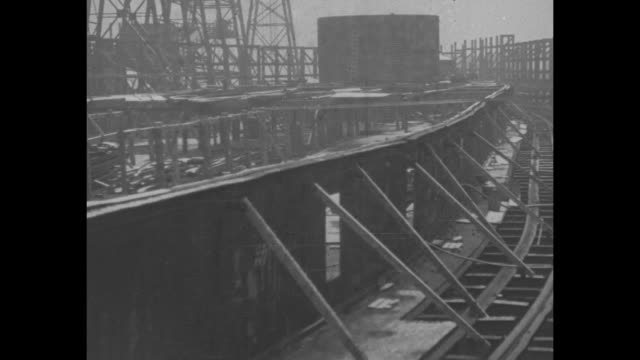 worker walking across snowcovered deck of unfinished battleship / ship under construction or construction halted / workers on ship / pan ship side... - costruttore navale video stock e b–roll