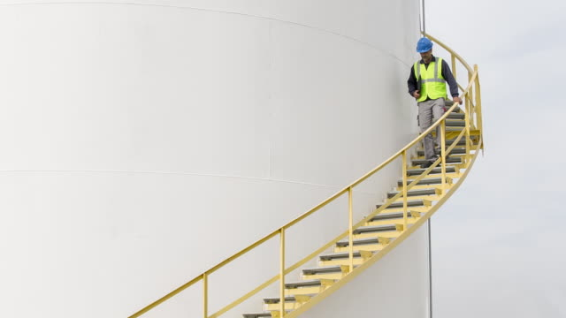 vidéos et rushes de ms worker walking down steps of a fuel storage tank - steps and staircases