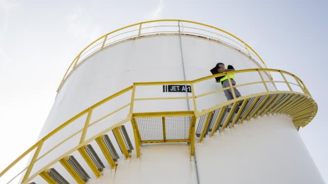 vidéos et rushes de ms worker walking down steps of fuel storage tank looking at notes - hommes d'âge moyen