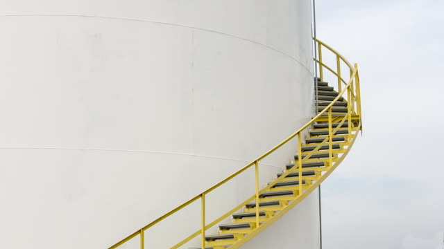 ms worker walking down steps of fuel storage tank - silo stock videos & royalty-free footage