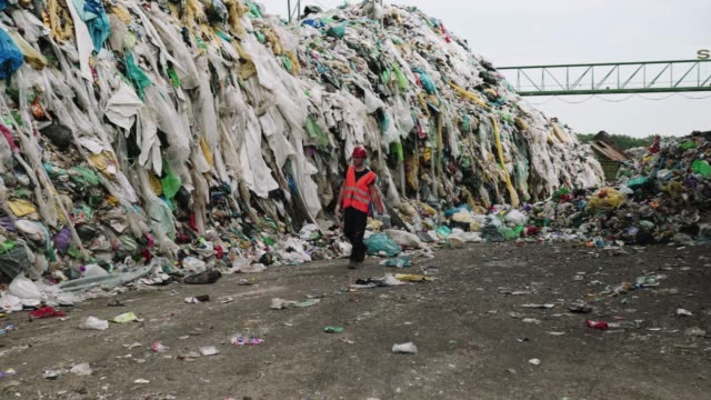 Worker walking past huge piles of garbage at waste disposal dump