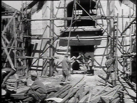 worker walking through bombedout street / workers erecting scaffolding / worker examining stack of bricks / worker nailing down shingles on a roof - 戦後点の映像素材/bロール