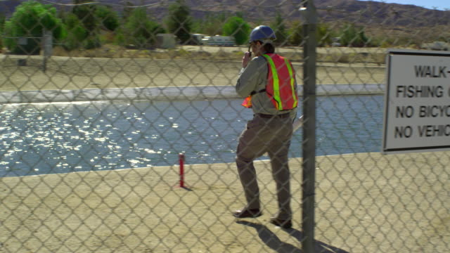 WS, PAN, Worker walking through fence into aqueduct area, Palmdale, California, USA