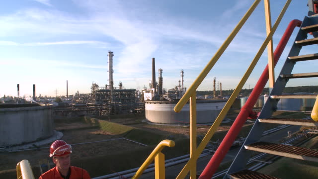 ws tu worker walking up stairs with holborn refinery in background / hamburg, germany - only mature men stock videos & royalty-free footage