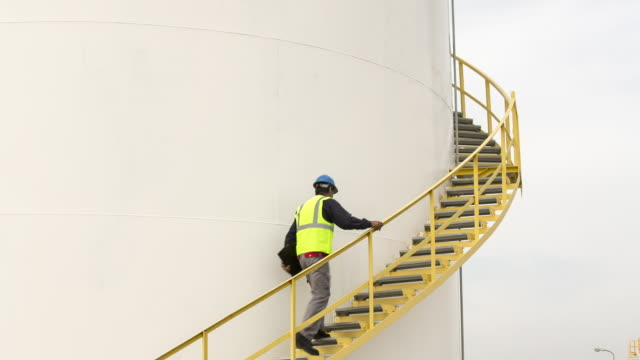 ms worker walking up steps of a fuel storage tank - fuel storage tank stock videos and b-roll footage