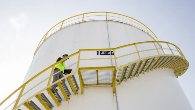 ms worker walking up steps of fuel storage tank looking at notes - fuel storage tank stock videos and b-roll footage