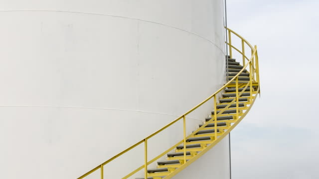 ms worker walking up steps of fuel storage tank stops to check his notes - fuel storage tank stock videos and b-roll footage