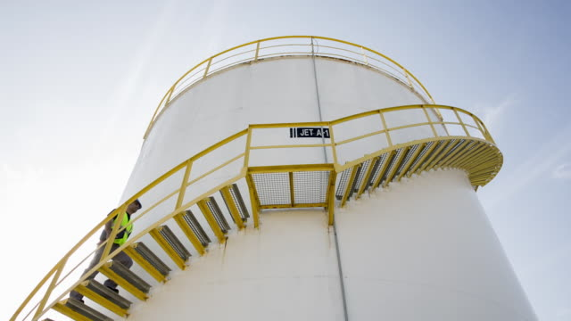worker walking up steps of fuel storage tank - fuel storage tank stock videos and b-roll footage
