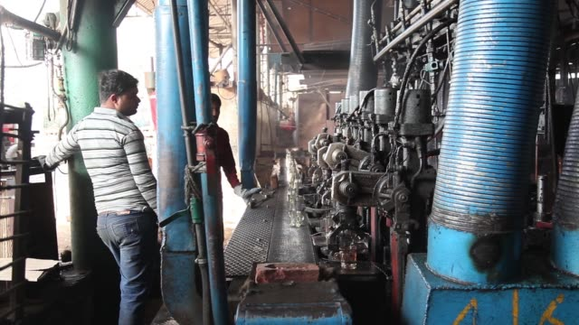 a worker walks near a molding machine at a pooja group of glass industries factory in ferozabad uttar pradesh india on saturday feb 21 2015 a worker... - uttar pradesh stock videos and b-roll footage