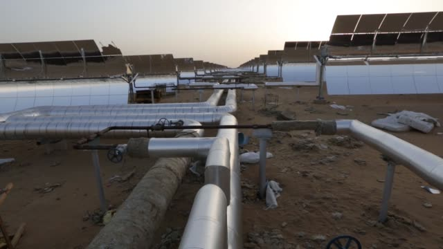worker walks past solar field pipes which connect to a parabolic trough at the godawari solar-thermal power plant, operated by godawari green energy... - reflector stock videos & royalty-free footage