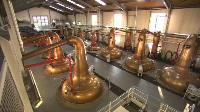 a worker walks through a whiskey distillery. - distillery still stock videos & royalty-free footage