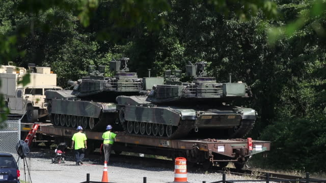 a worker washes one of two m1a1 abrams tanks that are loaded on flatbed rail cars at a csx railyard on july 2 2019 in washington dc president trump... - präsident der usa stock-videos und b-roll-filmmaterial