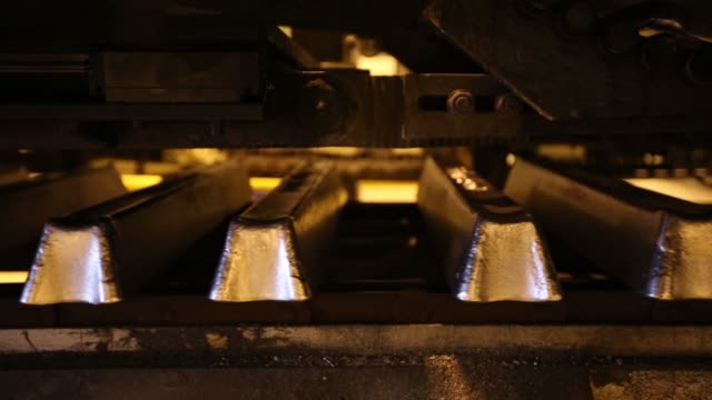 a worker watches as aluminum ingots cool as they pass along the production line in the foundry at the irkutsk aluminium smelting plant operated by... - aluminium stock videos & royalty-free footage