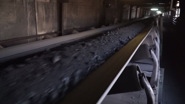 a worker watches as coal moves along a conveyor belt at the main coal processing building at the pavlogradska coal preparation plant operated by dtek... - ukraine stock-videos und b-roll-filmmaterial