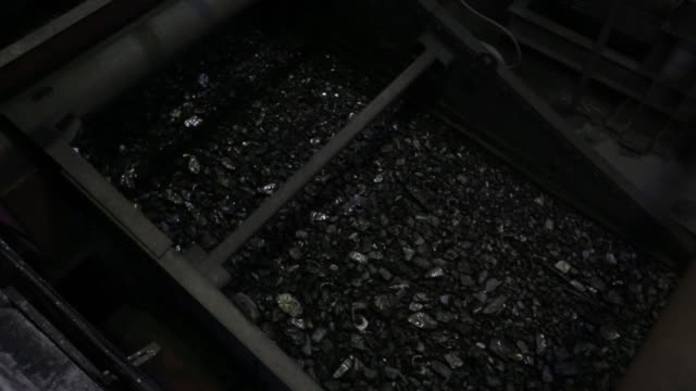 vidéos et rushes de a worker watches as coal passes along a conveyor belt in the dressing mill at the sibir coal processing plant operated by oao mechel mining a unit of... - mineur de charbon