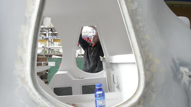 a worker wearing a face mask sands a fiberglass part at a king's fibreglass pty ltd facility in melbourne australia on wednesday aug 17 workers chat... - fibreglass stock videos and b-roll footage
