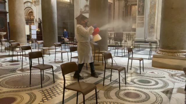 a worker wearing a protection suit sprays disinfectants during a sanification of the basilica of santa maria in trastevere as part of preparations... - chiesa video stock e b–roll