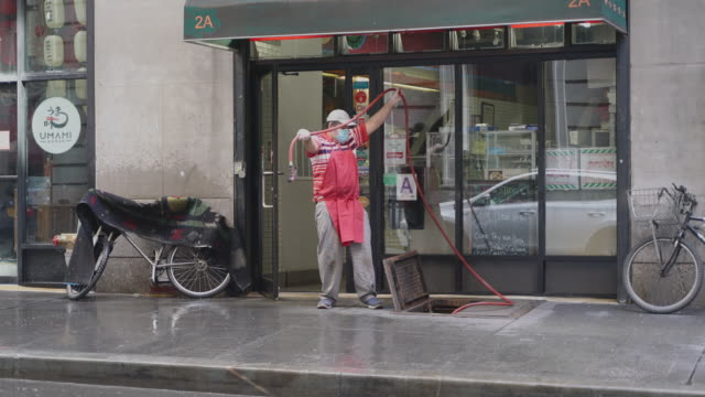 a worker wearing a protective face mask packing the cleaning equipment after disinfecting the sidewalk in front of hanover gourmet deli in manhattan... - large group of objects stock videos & royalty-free footage
