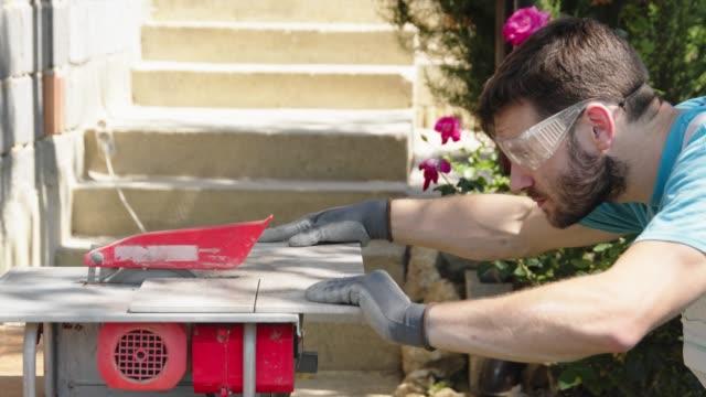 vídeos de stock e filmes b-roll de worker wearing protective glasses cutting a tile - cerâmica