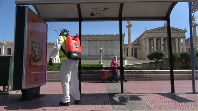 a worker wearing protective suits and mask disinfects a bus stop in the center of the greek capital on april 09 2020 in athens greece greece joined... - greek flag stock videos & royalty-free footage