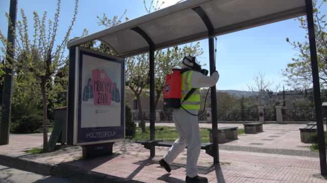 worker wearing protective suits and mask, disinfects a bus stop in the center of the greek capital on april 09, 2020 in athens, greece. greece joined... - athens greece stock videos & royalty-free footage