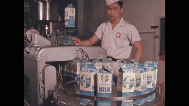 worker weighs cartons of milk for quality assurance in dairy plant - taipei stock videos & royalty-free footage