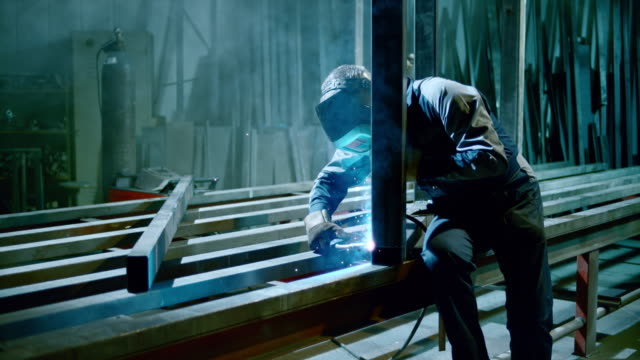 SLO MO DS Worker welding a metal frame