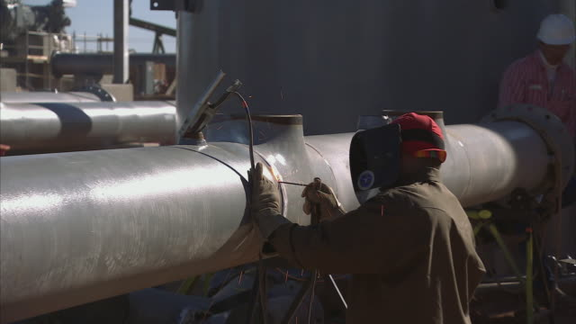 ZI Worker welding a seam on a silver pipeline / Texas, United States