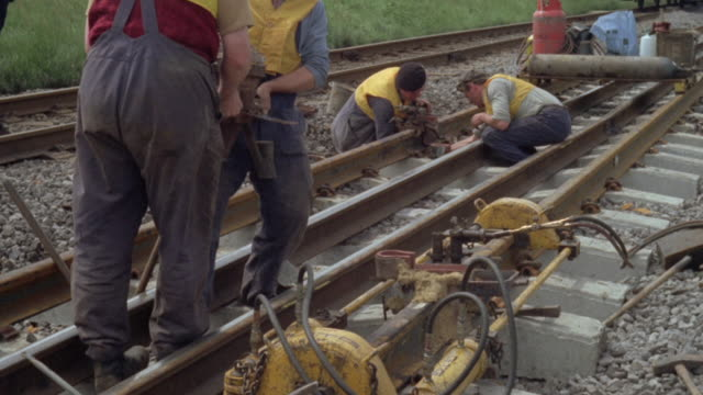 1969 MONTAGE Worker welding components to new tracks along the British Railways / United Kingdom