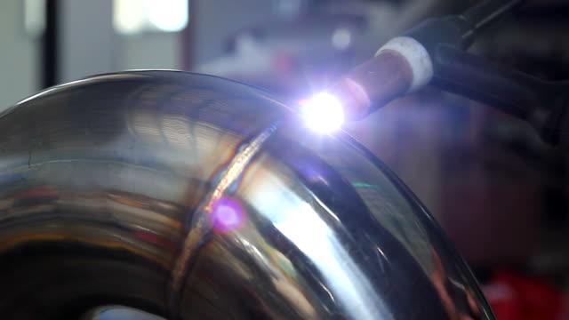 Worker welding metal exhaust pipe